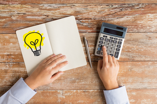 business idea, education, people and technology concept - close up of female hands with calculator, pen and lighting bulb drawing in notebook on table