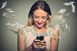 Happy woman using smartphone with dollar bills flying away from
