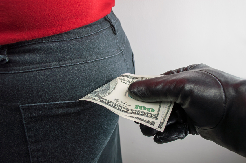 close up of a the hand of a thief stealing the dollars us to a woman